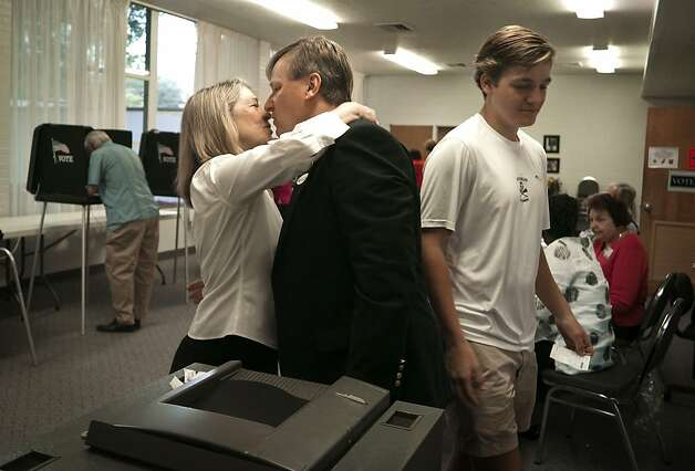 Dale Folwell, Republican candidate for lieutenant governor of North Carolina, center, gets a kiss from his wife, Synthia Folwell, after each voted in their home precinct in Winston-Salem, N.C., Tuesday, May 8, 2012. Their son, Stephen Folwell, right., had just voted for the first time.   (AP Photo/Winston-Salem Journal, David Rolfe) Photo: David Rolfe, Associated Press