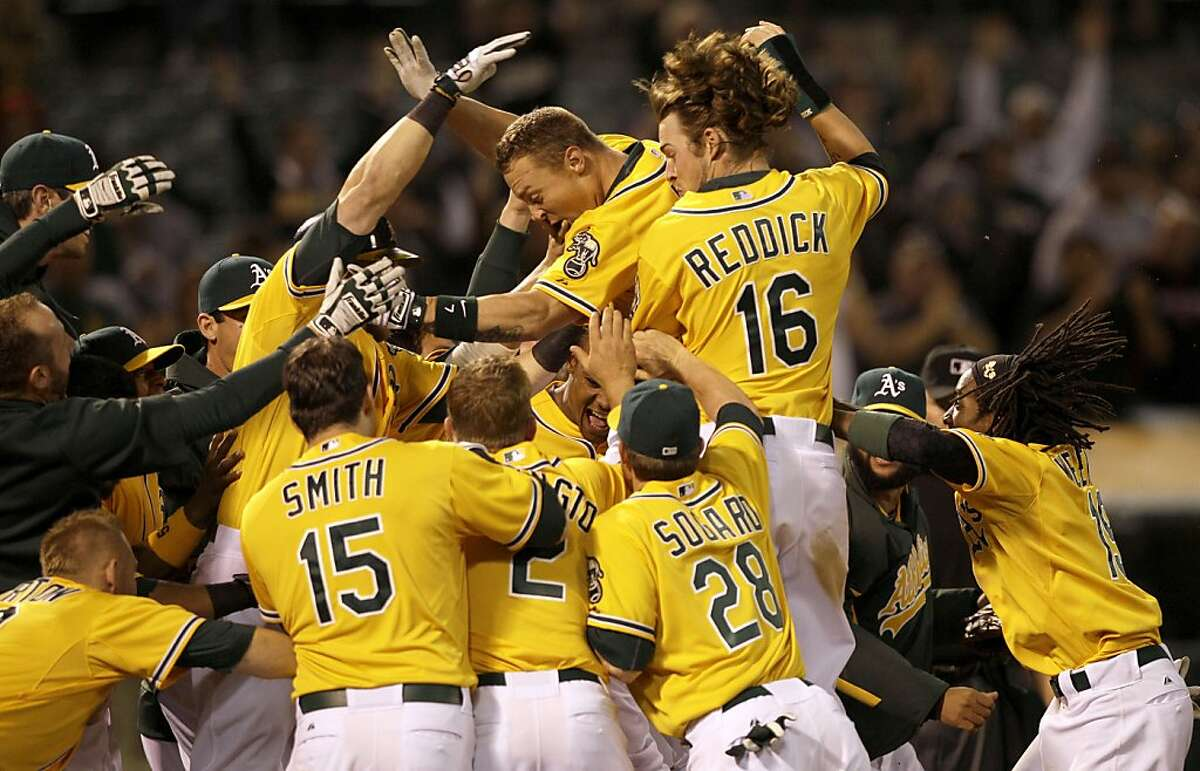 Oakland Athletics' Brandon Inge, center, top, celebrates after hitting a walk off grand slam home run off of Toronto Blue Jays pitcher Francisco Cordero during the ninth inning of a baseball game in Oakland, Calif., Tuesday, May 8, 2012. The Athletics won 7-3. (AP Photo/Jeff Chiu)