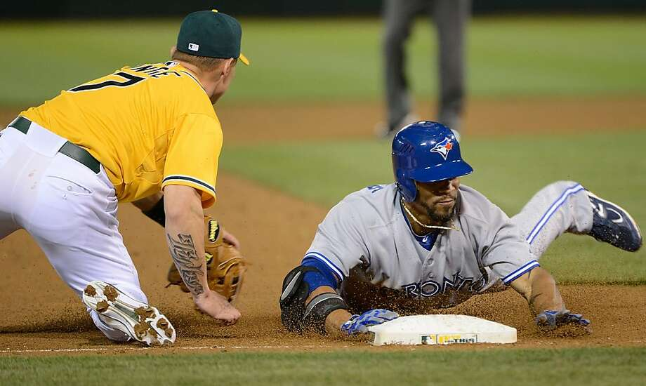 OAKLAND, CA - MAY 08:  Eric Thames #14 of the Toronto Blue Jays slides into third base head firs with a triple beating the throw to Brandon Inge #7 of the Oakland Athletics in the ninth inning at O.co Coliseum on May 8, 2012 in Oakland, California. The Athletics won the game 7-3 on a walk off grand-slam by Brandon Inge in the bottom of the ninth inning.  (Photo by Thearon W. Henderson/Getty Images) Photo: Thearon W. Henderson, Getty Images