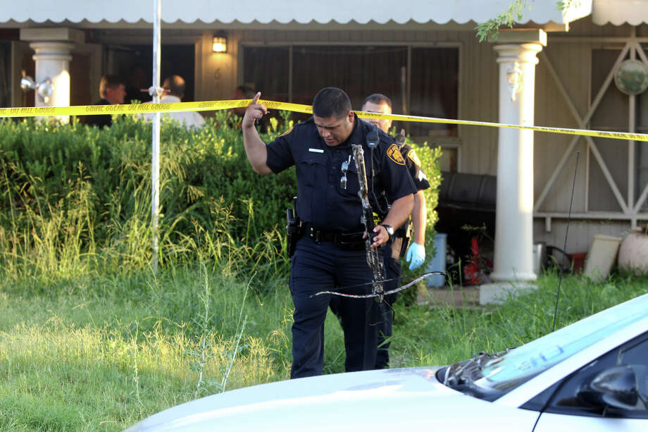 A San Antonio police officer removes a crossbow from the scene of a shooting with a hand gun that took place Wednesday morning about 6:15 a.m. at 643 Kopplow on the city's South Side. According to San Antonio police sergeant Bobby Bradley, the boyfriend of the homeowner's daughter fired a round that went through his own leg and then hit his girlfriend. The injuries are considered to be non-life threatening. The crossbow was not involved in the incident, but the officer on the scene said there is a policy in place to remove all weapons from apparent crime scene investigations. John Davenport/San Antonio Express-News Photo: SAN ANTONIO EXPRESS-NEWS