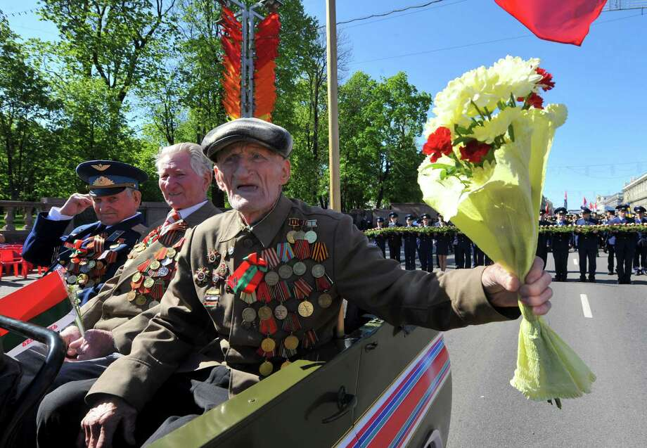 World War II veterans ride in  a vehicle in central Minsk on May 9, 2012, during Victory Day celebrations. Russia and ex-Soviet republics marked today the 67 years since the Soviet victory over Nazi Germany in World War II. AFP PHOTO / VICTOR DRACHEVVICTOR DRACHEV/AFP/GettyImages Photo: VICTOR DRACHEV, AFP/Getty Images / AFP