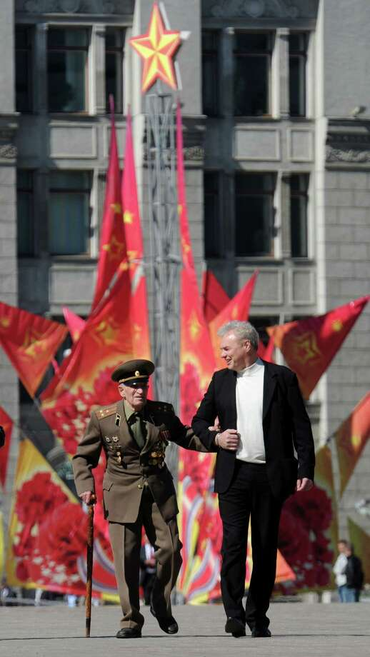 A man helps an eldelrly World War II veteran to walk  in central Minsk on May 9, 2012, during Victory Day celebrations. Russia and ex-Soviet republics marked today the 67 years since the Soviet victory over Nazi Germany in World War II. AFP PHOTO / VICTOR DRACHEVVICTOR DRACHEV/AFP/GettyImages Photo: VICTOR DRACHEV, AFP/Getty Images / AFP