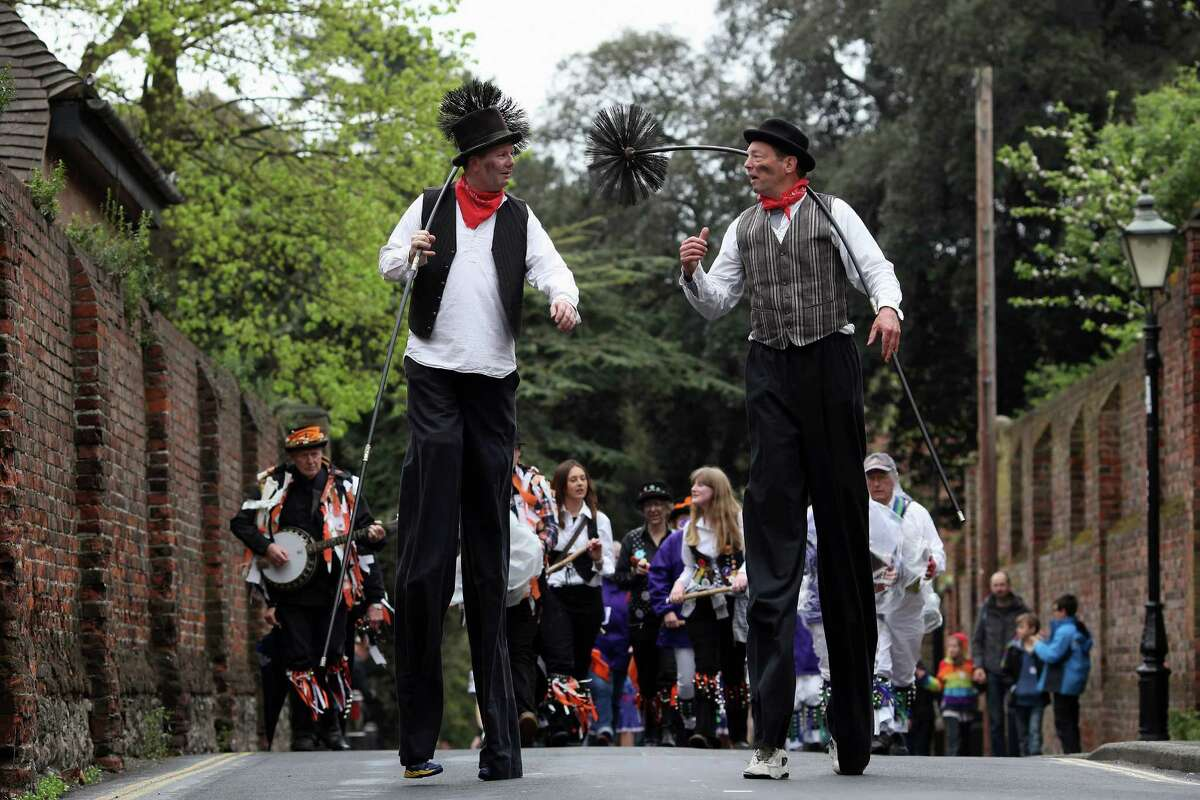 ROCHESTER, ENGLAND - MAY 07: Men dressed as chimney sweeps on stilts take part in the annual Sweeps Festival on May 7, 2012 in Rochester, England. The three day annual Sweeps Festival in Rochester dates back 400 years and was originally the one day in the year that the chimney sweeps could afford time off to celebrate the coming of spring. This year marks the festival's 32nd year since its reintroduction in 1980, with traditional activities including Morris dancers, who parade to Rochester Castle, and a Jack-in-the-Green ceremony.