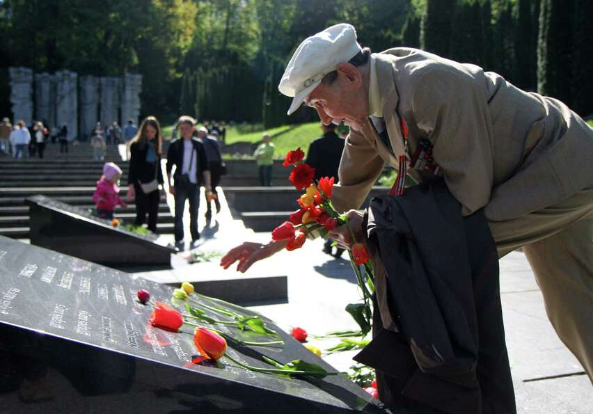 Usirov Usthan, a 92-year-old veteran of World War II, lays flowers on May 9, 2012 by the monument of