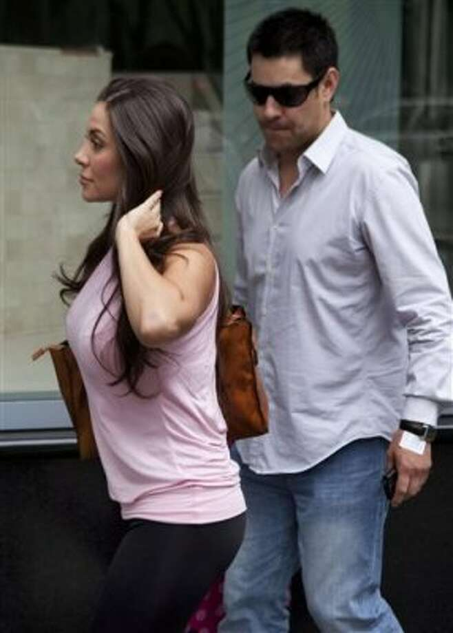 Model Julia Orayen, left, from Argentina, is watched by a man as she leaves after an interview in Mexico City, Tuesday, May 8, 2012. Orayen has posed nude for Playboy and appeared barely dressed in other media, but she made her mark on Mexican minds Sunday night by carrying an urn filled with bits of paper determining the order that candidates would speak during a presidential debate.  (AP Photo/Eduardo Verdugo) (AP)