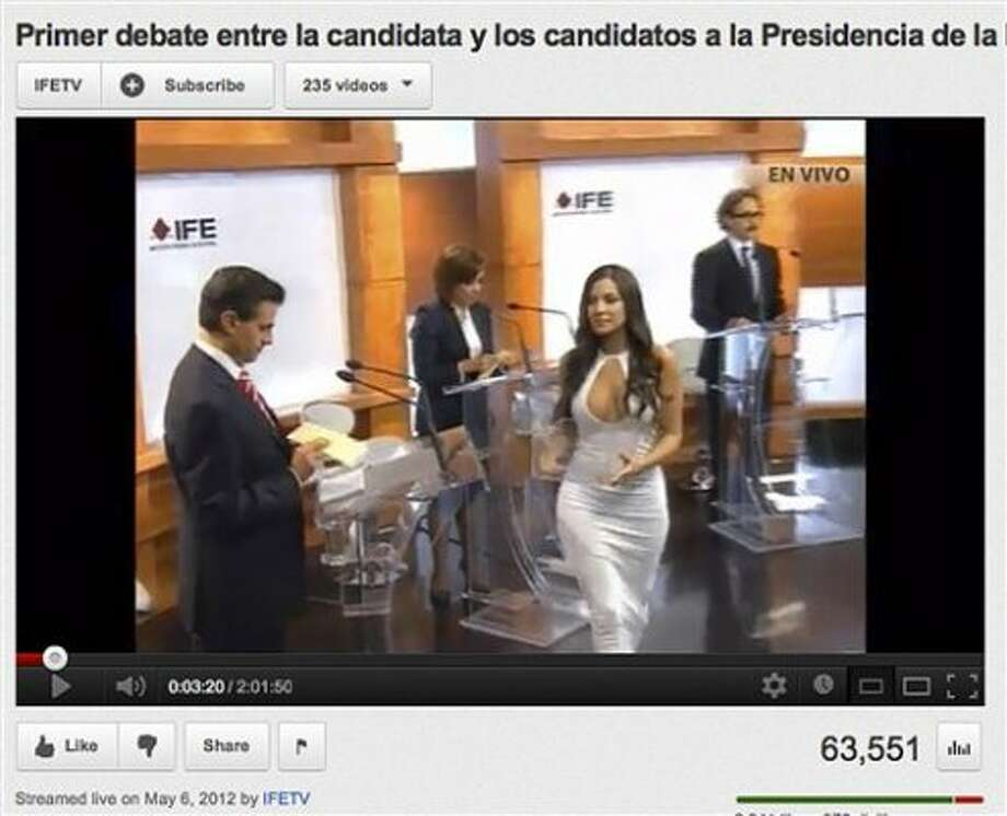 In this screen grab taken from Mexico's Federal Electoral Institute's YouTube channel, Julia Orayen, second from right, carries a box to presidential candidates containing paper for them to take to assign their speaking order at the start of a presidential candidate debate in Mexico City, Sunday, May 6, 2012. The Federal Election Commission, which organized the debate, said an independent producer had hired the former model, and acknowledged that her dress choice was a mistake. (AP Photo/IFETV via YouTube) (ASSOCIATED PRESS)