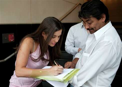 Model Julia Orayen, left, from Argentina, signs an autograph after an interview in Mexico City, Tuesday, May 8, 2012. Orayen has posed nude for Playboy and appeared barely dressed in other media, but she made her mark on Mexican minds Sunday night by carrying an urn filled with bits of paper determining the order that candidates would speak during a presidential debate.  (AP Photo/Eduardo Verdugo) Photo: Associated Press