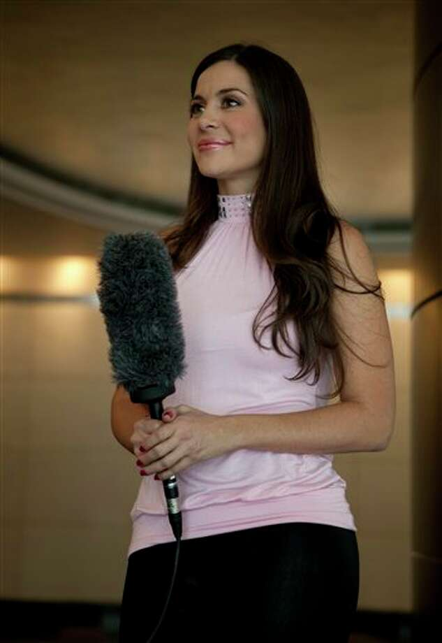 Model Julia Orayen, from Argentina, holds a microphone during an interview in Mexico City, Tuesday, May 8, 2012. Orayen has posed nude for Playboy and appeared barely dressed in other media, but she made her mark on Mexican minds Sunday night by carrying an urn filled with bits of paper determining the order that candidates would speak during a presidential debate.  (AP Photo/Eduardo Verdugo) Photo: Associated Press