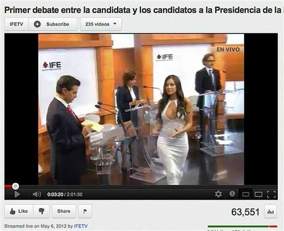 In this screen grab taken from Mexico's Federal Electoral Institute's YouTube channel, Julia Orayen, second from right, carries a box to presidential candidates containing paper for them to take to assign their speaking order at the start of a presidential candidate debate in Mexico City, Sunday, May 6, 2012. The Federal Election Commission, which organized the debate, said an independent producer had hired the former model, and acknowledged that her dress choice was a mistake. (AP Photo/IFETV via YouTube) Photo: Associated Press