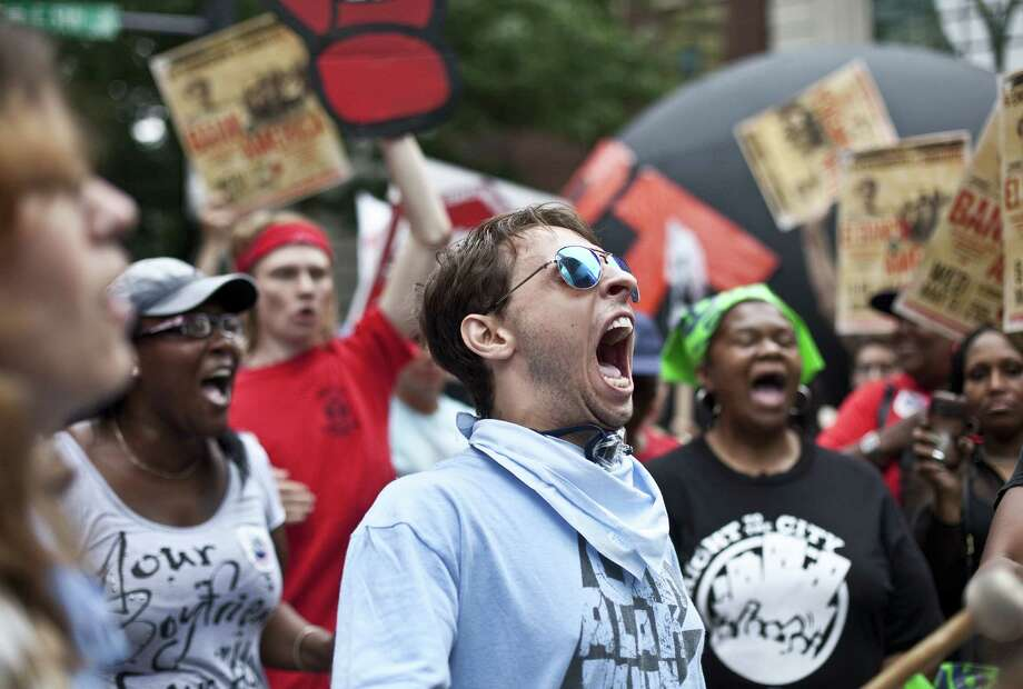An activist shouts while protesting outside of the annual Bank of America Corp. shareholders meeting on May 9, 2012 in Charlotte, North Carolina. Protesters from several movements including the 99 Percent Power movement converged on the annual shareholders meeting to protest a range of issues and actions. Photo: John W. Adkisson, Getty Images / 2012 Getty Images