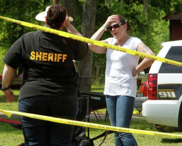 Liberty County Sheriff Department officers speak with April Davis right the mother of 2 1/2 year-old Devon Davis outside her home as law enforcement officers and volunteers search for her son after he went missing Tuesday, Wednesday, March 28, 2012, in Cleveland. Photo: Houston Chronicle