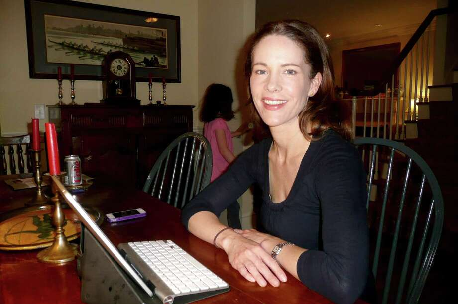 "Greenwich resident and author Beatriz Williams, a mother of four, just had her first novel published this week. Williams wrote the book, ""Overseas,""  on her iPad sitting at her dining room table, above, or in a local Starbucks. ""I tend to work in creative spurts,"" she says. In the backround, running through the dining room, is Williams' daughter Anna, 9. Photo: Anne W. Semmes"