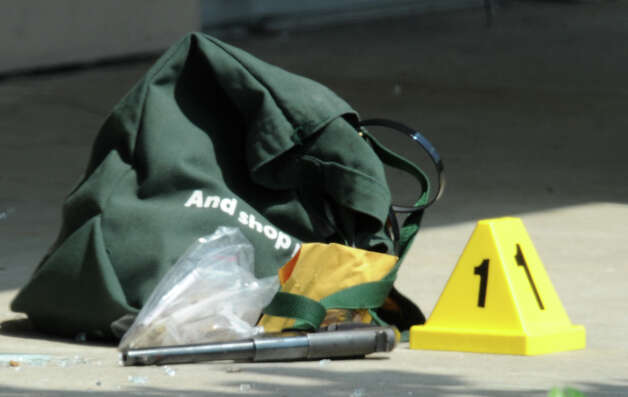 The robbers gun was found near some of his belongings that were dropped as he walked outside and collapsed from four gunshot wounds.  Photo taken Wednesday, May 9, 2012 Guiseppe Barranco/The Enterprise Photo: Guiseppe Barranco, STAFF PHOTOGRAPHER / The Beaumont Enterprise