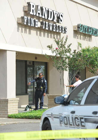 Beaumont Police investigate the scene of a shooting at Randy's Fine Jewelers Wednesday. The shooting stemmed from a botched robbery that left the suspect with four bullet wounds and the owner Randy Flatau with one bullet wound in the leg.  Photo taken Wednesday, May 9, 2012 Guiseppe Barranco/The Enterprise Photo: Guiseppe Barranco, STAFF PHOTOGRAPHER / The Beaumont Enterprise