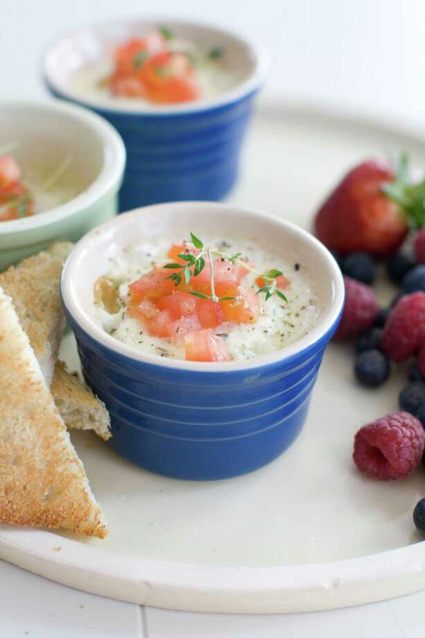 Baked eggs with toast for dipping and fruit salad are seen in Concord, N.H. (AP Photo/Matthew Mead) Photo: Matthew Mead