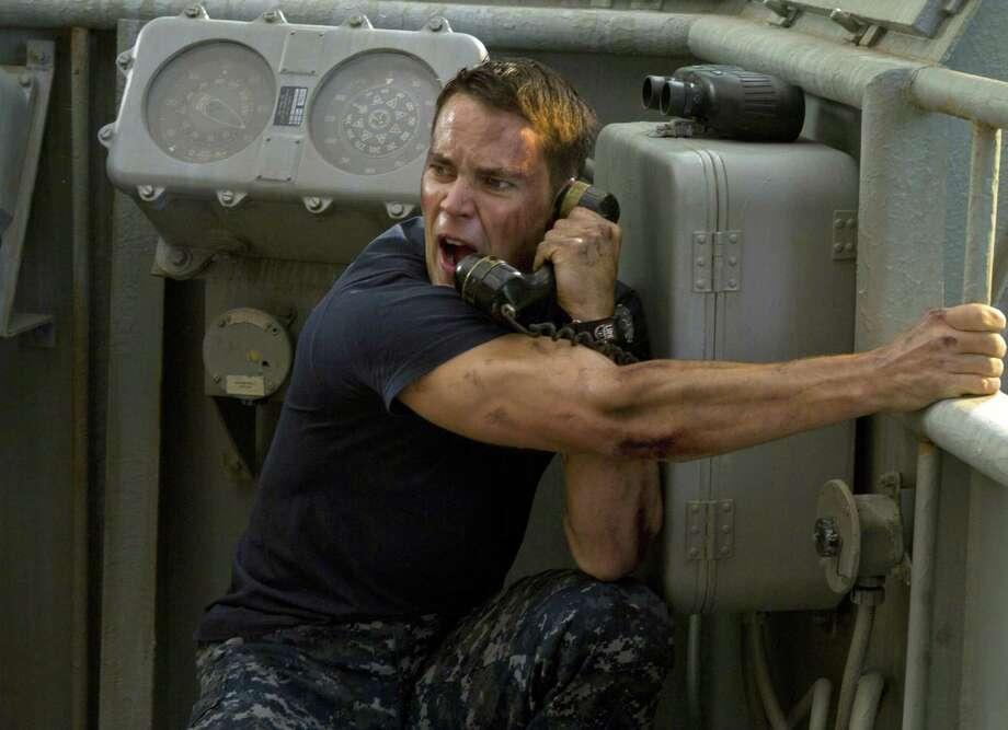 "In this film image released by Universal Pictures, Taylor Kitsch is shown in a scene from ""Battleship."" The Hasbro Inc. game using plastic pegs and ships was once a way for kids to while away lazy summer afternoons. But as it debuts in Europe on April 11, ""Battleship"" the movie has become a potential franchise sporting Michael Bay-inspired special effects, aliens invading Earth, a bikini-model actress, superstar Rihanna and, of course, lots of guns. Photo: AP"