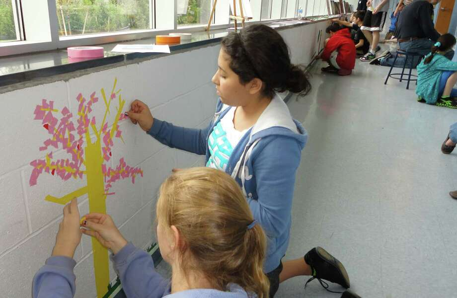 "Fiona McElroy, right, and Marielle Awad, both 13-year-old eighth-graders at Fairfield Woods Middle School used colored electrical tape to create a dogwood tree in the ""Our Town"" section of a corridor where students were invited to make tape murals May 3 during the 11th Bi-Annual Arts in Action program. Photo: Meg Barone / Fairfield Citizen freelance"