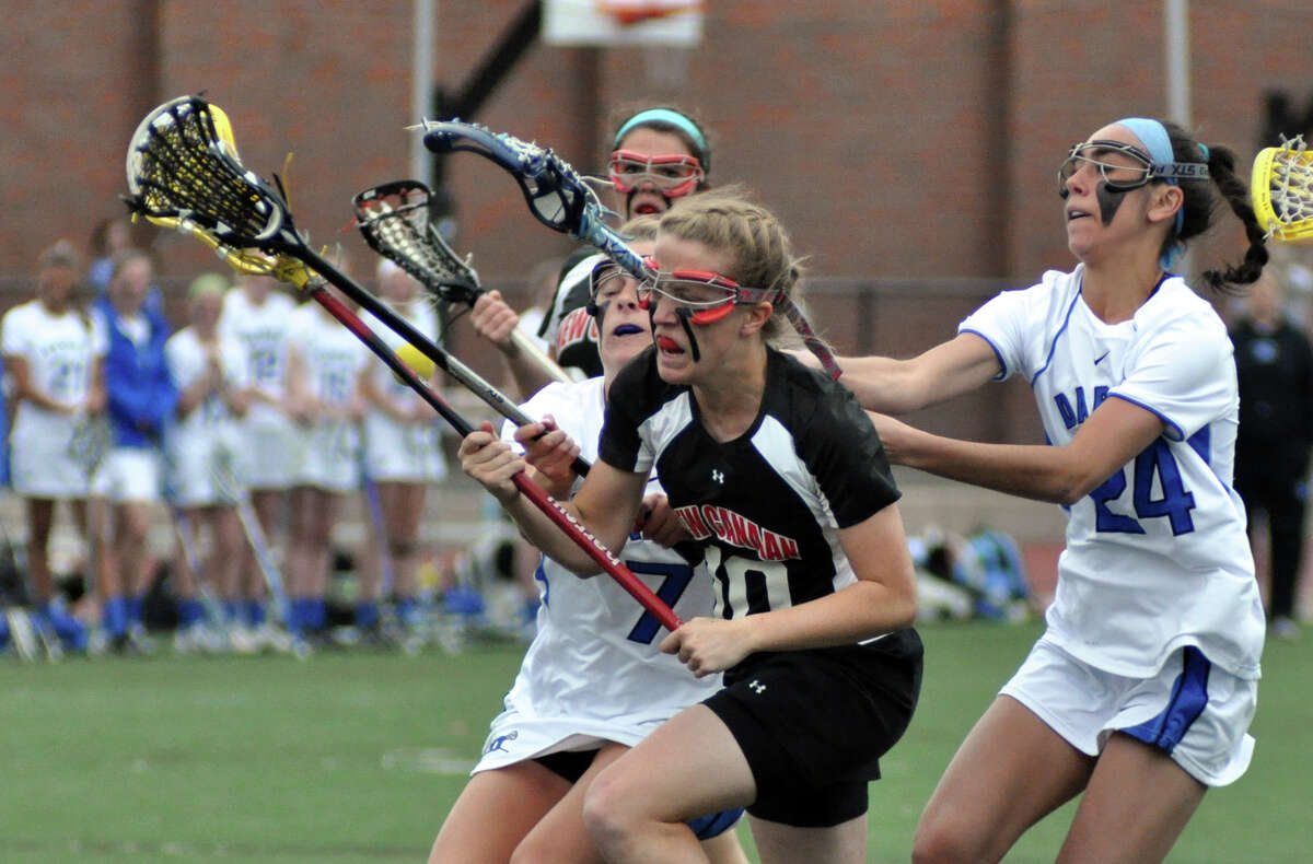 Darien's Emily Tropsa (7) and Vanessa Budd (24) defend against New Canaan's Sarah Mannelly (10) during the girls lacrosse game at Darien High School on Wednesday, Apr. 18, 2012.