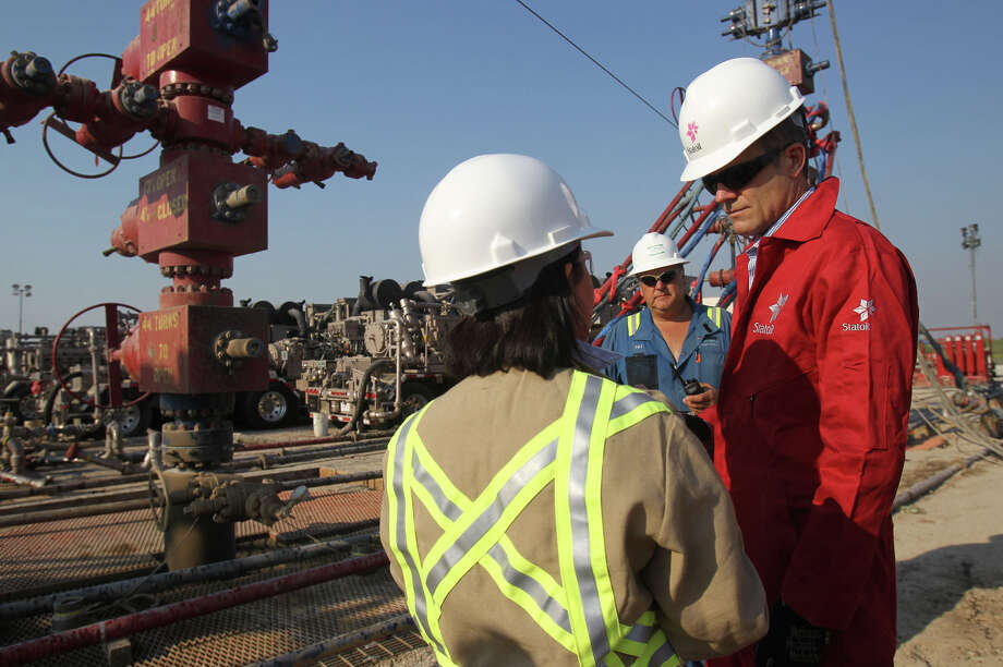 Helge Lund (right), CEO of Norwegian energy company Statoil, speaks with Talisman Energy hydraulic fracturing specialist Nabila Larsen at a site near Cotulla last year. One expert estimates that there's at least 30 years of production in the Eagle Ford. Photo: San Antonio Express-News File Photo