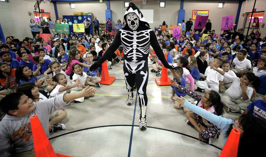 Lucha Libre wrestlers Mini Park (in costume) and Rocky Romero greet students at De Zavala Elementary during an anti-bullying event Wednesday, May 9, 2012. They also promoted Lucha Libre USA's Masked Warriors Live Tour, which stops Friday at the Alamodome. Photo: BOB OWEN, San Antonio Express-News / © 2012 San Antonio Express-News