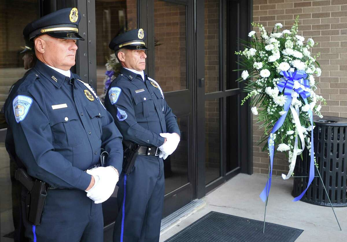 Kolin Burmaster, left, and Sgt. Marc Levy, right, stand with the wreath that would be placed at the base of the memorial. Fallen Beaumont Police Officer Bryan Hebert's badge was added to the police officer memorial in front of the Beaumont Police station on Wednesday morning, May 9, 2012. A new female police officer statue was also unveiled. The 2012 dedication comes the week before National Police Week, when the Hebert family will be in Washington D.C. to attend a national memorial. Dave Ryan/The Enterprise