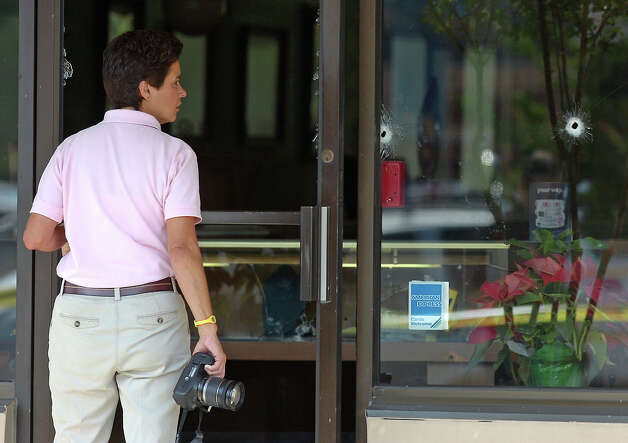 A Beaumont Police crime scene investigator walks past two bullet holes in the front window of Randy's Fine Jewelers on Wednesday. The store was the scene of a robbery that turned into a shootout after the store owner Randy Flatau shot the robber four times. Flatau was also shot in the leg once. Both men are said to be in stable condition. Photo taken Wednesday, May 9, 2012 Guiseppe Barranco/The Enterprise Photo: Guiseppe Barranco, STAFF PHOTOGRAPHER / The Beaumont Enterprise