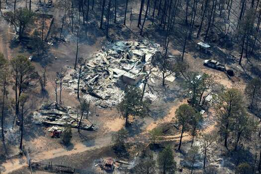 A burned out home is seen at an intersection in this Tuesday Sept. 6, 2011 aerial image taken over the wildfires in the Bastrop, Texas area.    (William Luther/wluther@express-news.net) Photo: WILLIAM LUTHER, SAN ANTONIO EXPRESS-NEWS / 2011 SAN ANTONIO EXPRESS-NEWS