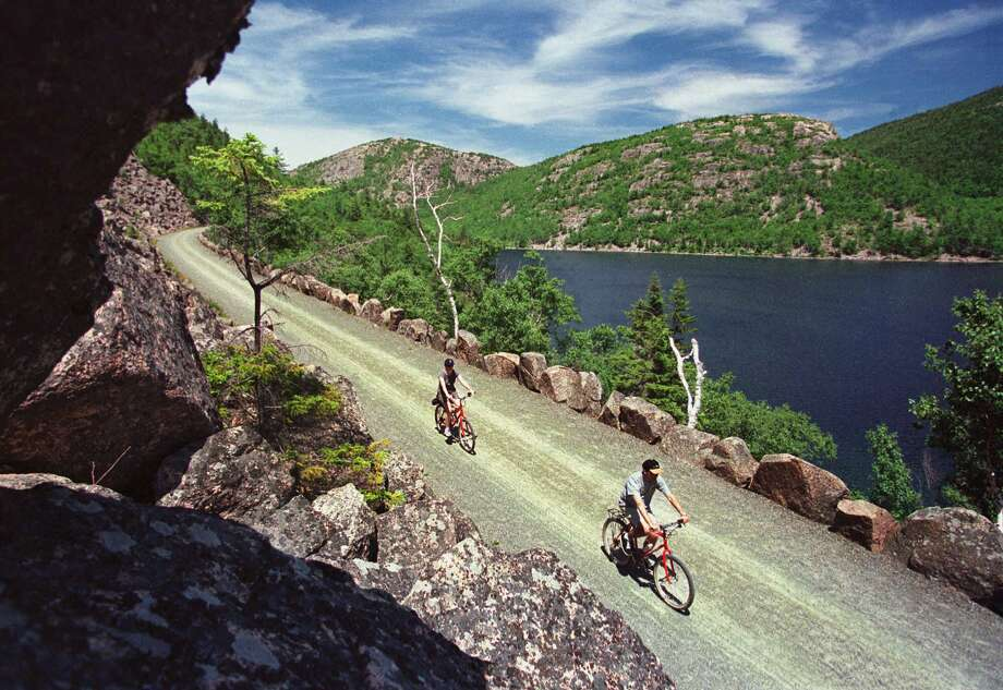 Bicyclists glide past a vista overlooking Jordan Pond and the Bubbles Mountains on a carriage road at Acadia National Park, near Bar Harbor, Maine. Photo: ROBERT F. BUKATY / AP