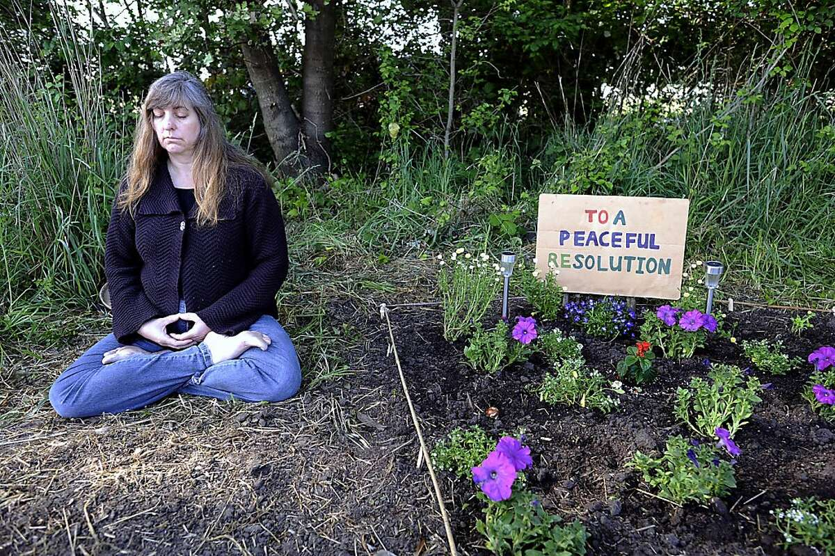 Leah Kenaga, wife of UC Berkeley researcher Damon Lisch, sits in silent meditation in oppisition to the occupation of the farm. Occupiers with Occupy the Farm braced for a possible police raid at the Gill Tract in Albany, CA Wednesday May 9th, 2012.
