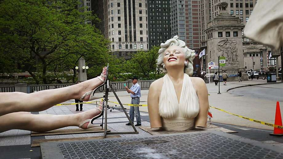 A passerby photographs one of the dismantled pieces of 'Forever Marilyn', a sculpture by Seward Johnson, as it is prepared for removal from Pioneer Court May 8, 2012 in Chicago, Illinois. The stainless steel and aluminum sculpture, which stands 26 feet tall and weighs 34,000 pounds, was inspired by Marilyn Monroe's iconic scene in the 1955 movie 'The Seven Year Itch'. The sculpture, which has been on display in Chicago since last July, will next be displayed in Palm Springs, California.  (Photo by Scott Olson/Getty Images) Photo: Scott Olson, Getty Images