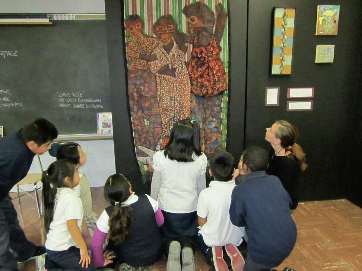 A group of Roosevelt School students, with art teacher Melissa Abenante (far right), view a batik work by Nigerian artist Tunde Odunlade.