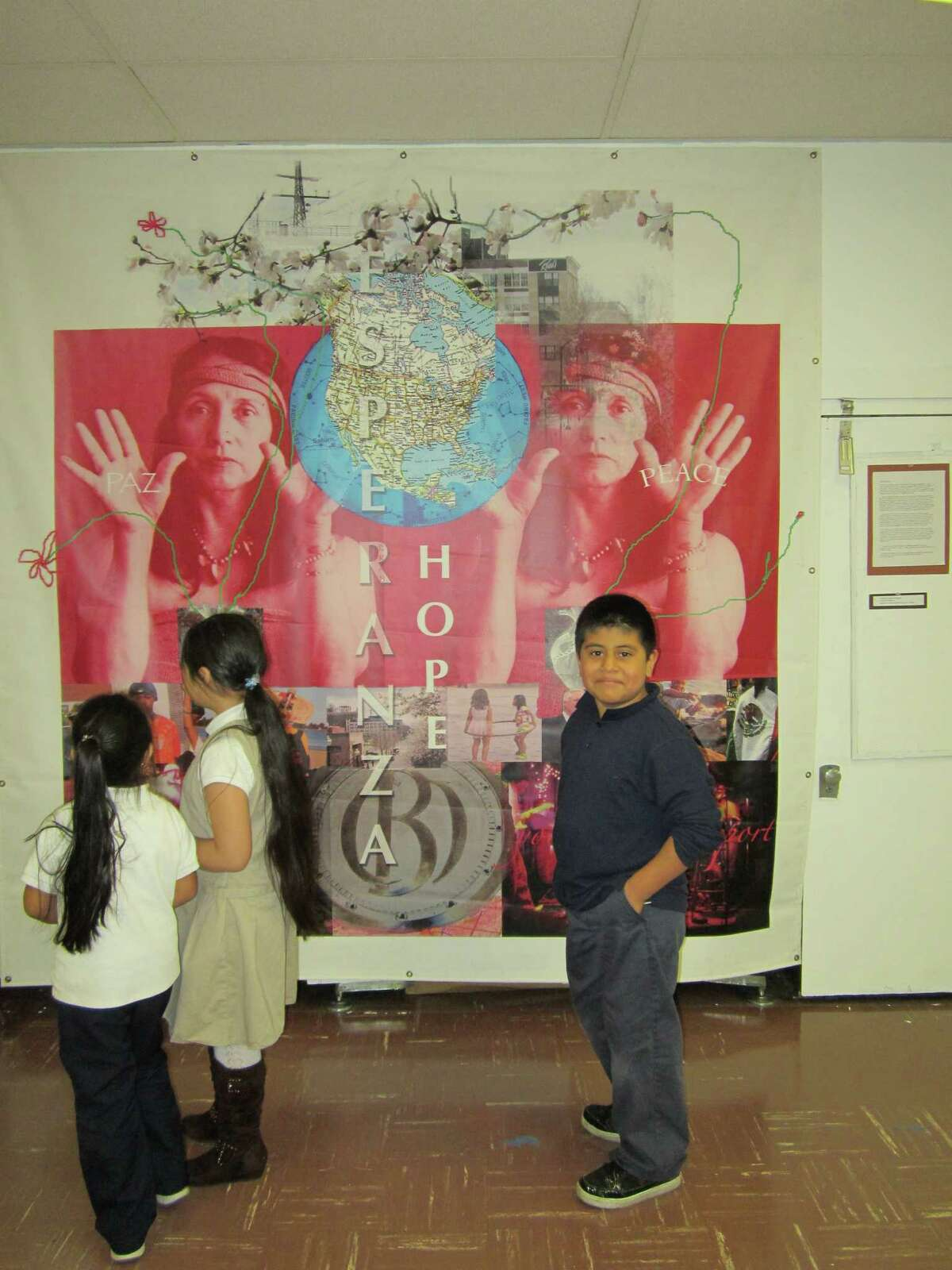 A group of Roosevelt School students view a mural banner by Bridgeport artist Yolanda Petrocelli in the school's art gallery.