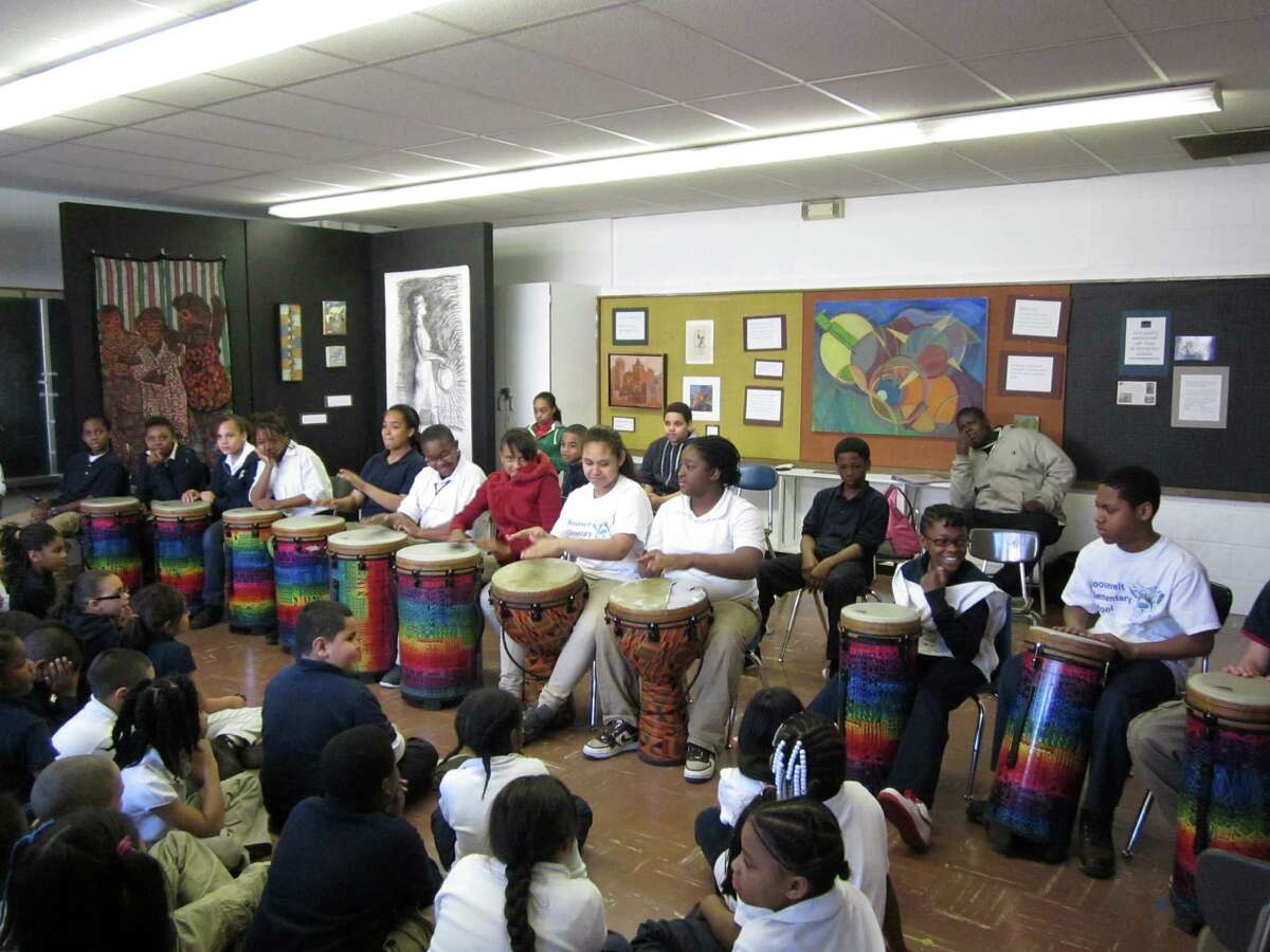 Students at Roosevelt School attend a drumming performance in the school's art gallery.