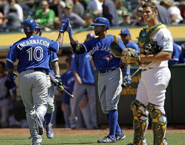 Toronto Blue Jays' Edwin Encarnacion (10) is congratulated by Eric Thames, center, after hitting a solo home run as Oakland Athletics catcher Anthony Recker, right, stands at the plate during the eighth inning of a baseball game on Wednesday, May 9, 2012 in Oakland, Calif.  Toronto won 5-2. (AP Photo/Marcio Jose Sanchez) Photo: Marcio Jose Sanchez, Associated Press