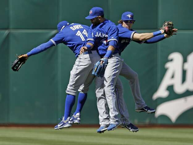 Toronto Blue Jays' Rajai Davis (11), Jose Bautista, center, and Colby Rasmus, right, celebrate after their 5-2 win over the Oakland Athletics in a baseball game on Wednesday, May 9, 2012 in Oakland, Calif.   (AP Photo/Marcio Jose Sanchez) Photo: Marcio Jose Sanchez, Associated Press