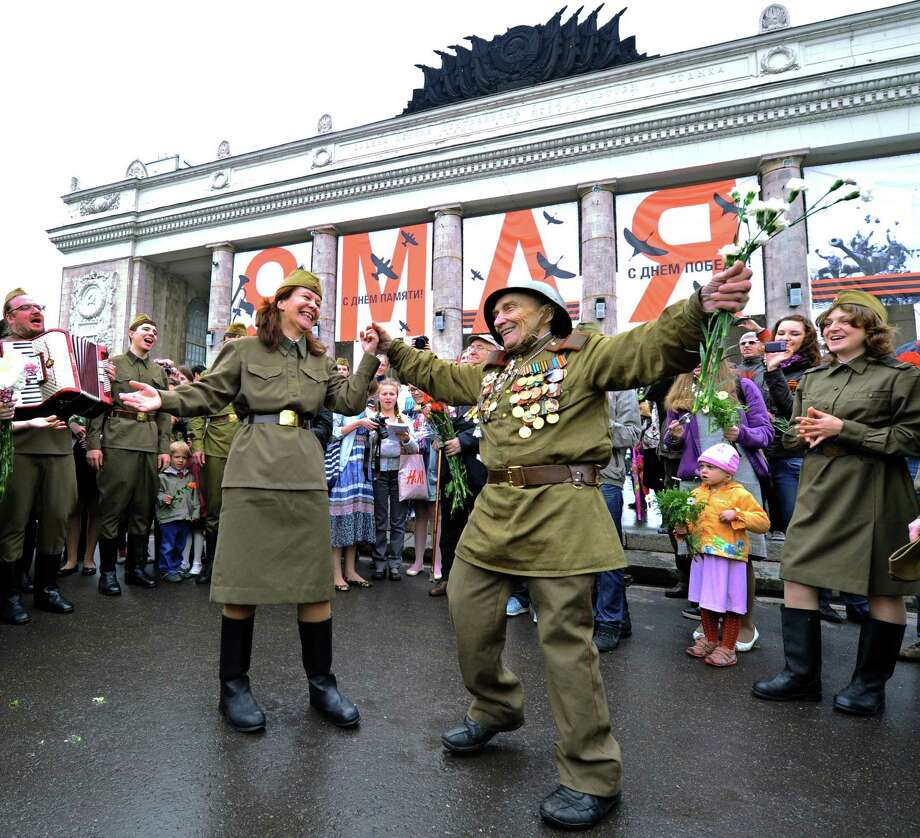 Wearing World War II-era Red Army field uniform and medals a veteran (C) dances with actors  in Gorky park, a traditional veterans meeting place, in Moscow, on May 9, 2012. Thousands of Russian soldiers marched today across Red Square to mark the 67 years since the victory over Nazi Germany in World War II. Photo: YURI KADOBNOV, AFP/Getty Images / AFP