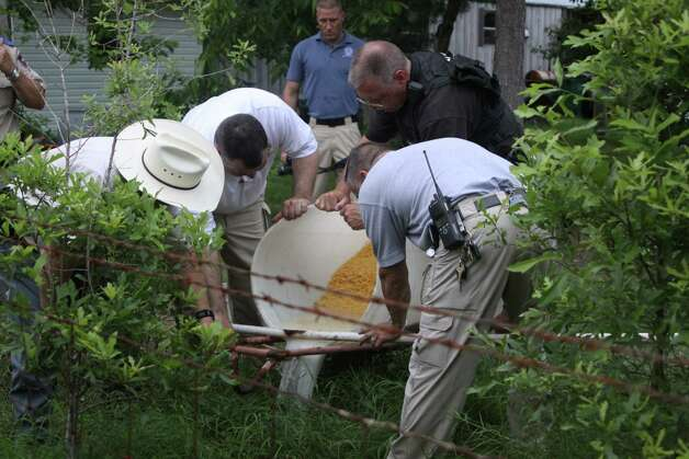 Deputies dispose of processing moonshine at a home on Harper Lane in Kountze Wednesday evening. Two were arrested and charged one count of possession of illicit distilled spirits and one count of possession of material of manufacture for illicit beverage. Photo: David Lisenby