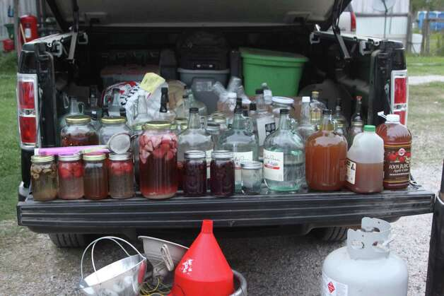 The Hardin County Sheriff's Office confiscated numerous containers of moonshine from a home on Harper Lane in Kountze Wednesday evening. Two were arrested and charged one count of possession of illicit distilled spirits and one count of possession of material of manufacture for illicit beverage. Photo: David Lisenby
