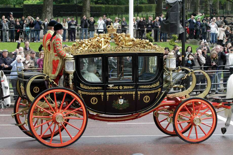 Britain's Queen Elizabeth II on a carriage departs Buckingham Palace on her way to  the Houses of Parliament for the State Opening, in London, Wednesday, May 9, 2012. Announcing the government's new legislative program Wednesday in an opulent pageant of pomp and politics, the queen said planned laws would introduce a smaller, mainly upper elected chamber. (AP Photo/Lefteris Pitarakis) Photo: Lefteris Pitarakis / AP