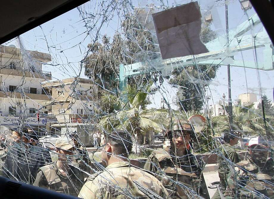 Syrian army soldiers, are seen through a damaged military truck window which was attacked by a roadside bomb, in Daraa city, southern Syria, on Wednesday May 9, 2012.   The explosion targeted the Syrian military truck just seconds after a team of U.N. observers passed by. An Associated Press reporter who was traveling in the U.N. convoy said three bloodied Syrian soldiers were rushed from the scene after Wednesday's blast, but the U.N. convoy was not hit. (AP Photo/Muzaffar Salman) Photo: Muzaffar Salman, Associated Press
