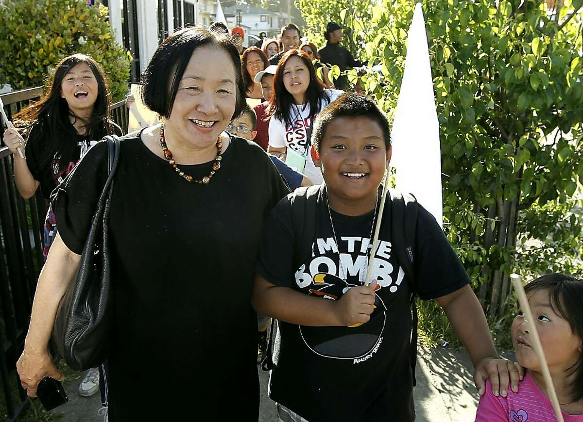 Mayor Jean Quan walks with fifth grader Sandler Saephan as they join parents and students for the Manzanita Community Peace Walk through the neighborhood near E. 27th Street and Fruitvale, in Oakland, Ca., on Wednesday May 9, 2012.