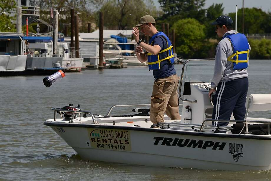 "In this provided photo, Andrew Tinka tosses an instrumented floating ""robot"" into the Sacramento river, while Kevin Weekly steadies the boat. Photo: Jerome Thai"