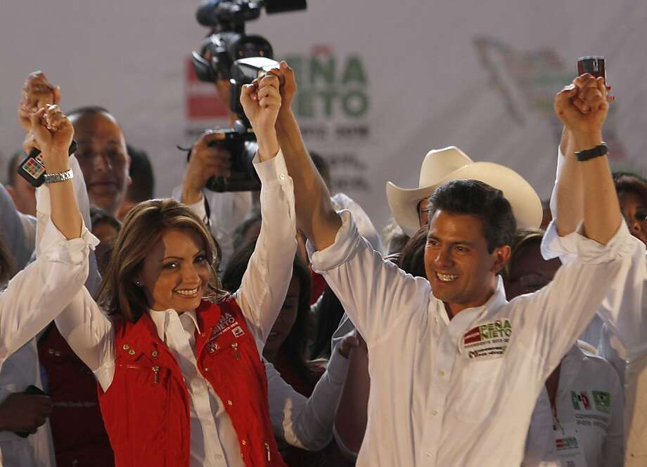 "In this April 28, 2012 photo, Mexican actress Angelica Rivera de Pena, left, and her husband Enrique Pena Nieto, presidential candidate for the Institutional Revolutionary Party, PRI, raise their arms at a campaign rally in Nezahualcoyotl, Mexico. Just months before an election Pena Nieto is expected to win, he and his wife, a popular soap opera star known as ""La Gaviota,"" or The Seagull, the nickname of one of her most popular characters, have not only become Mexican's most glamorous couple, they're also ushering in a new mix of politics and show business. (AP Photo/Marco Ugarte) Photo: Marco Ugarte, Associated Press"