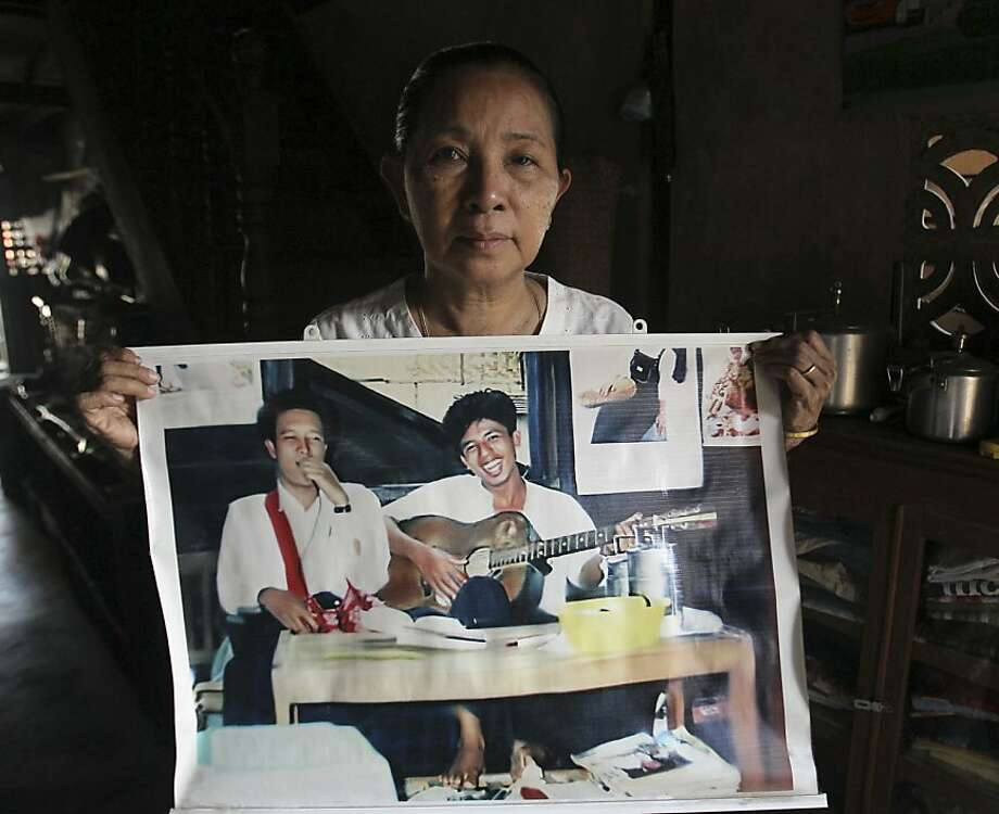 In this April 26,2012 photo, Myanmar San Myint, mother of former student activist Aye Aung, holds a picture of her son playing a guitar, in Yangon, Myanmar. In a remote concrete prison a three-day bus ride from home, Aye Aung spends each day as he has for nearly 14 years - a prisoner of conscience all but forgotten by the world. Although Myanmar's military-backed government has released hundreds of well-known dissidents over the past year as part of a startling series of reforms that have earned it lavish praise and an easing of sanctions, rights advocates say hundreds more like Aye Aung remain wrongfully locked away - their cases in danger of being forgotten amid rising hope for a more open, democratic nation. (AP Photo/Sakchai Lalit) Photo: Sakchai Lalit, Associated Press