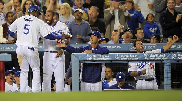 Los Angeles Dodgers' Juan Uribe, left, is congratulated by Matt Kemp, second from left, and manager Don Mattingly, second from right, while Andre Ethier reacts after Tony Gwynn hit a three-run triple during the fourth inning of a baseball game against the San Francisco Giants, Wednesday, May 9, 2012, in Los Angeles. (AP Photo/Mark J. Terrill) Photo: Mark J. Terrill, Associated Press