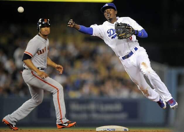 Los Angeles Dodgers shortstop Dee Gordon, right, throws out San Francisco Giants' Melky Cabrera at first as Brandon Crawford watches during the fourth inning of their baseball game, Wednesday, May 9, 2012, in Los Angeles. (AP Photo/Mark J. Terrill) Photo: Mark J. Terrill, Associated Press