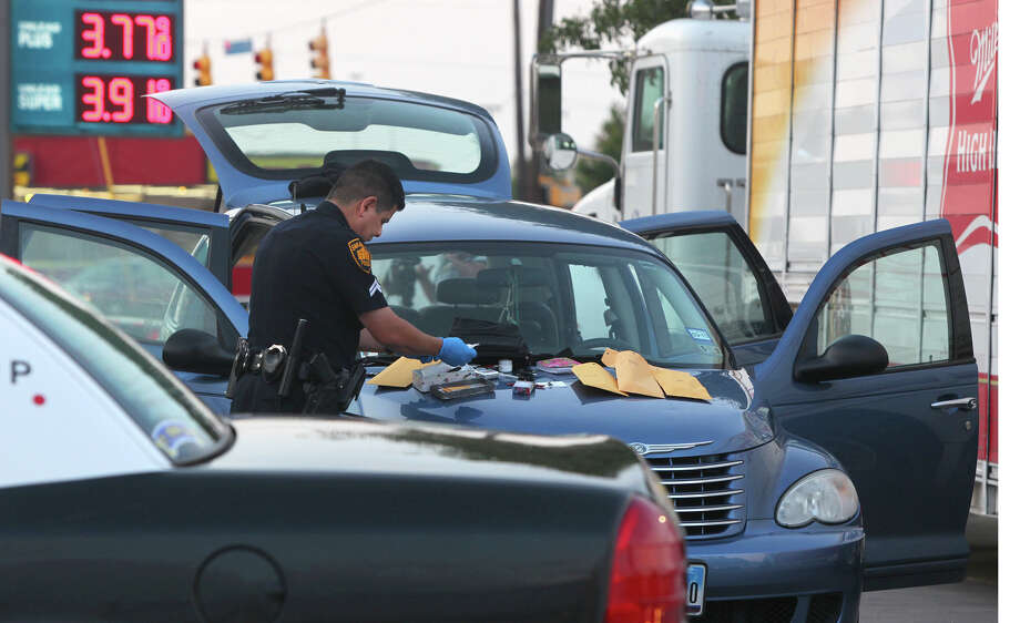 San Antonio police uniformed evidence detective Robert Neaves puts items in envelopes found in a Chrysler SUV at a Valero station on the 7,000 block of Blanco road that was allegedly used in a crime spree at some North Side convenience stores. Three suspects were apprehended Thursday morning May 10, 2012 after it was reported one suspect wielded a knife at a convenience store on San Pedro and that another suspect attempted to steal an 18-pack of beer from a Miller beer truck at a Valero station on the 7,000 block of Blanco road. It was reported that a female off-duty Department of Public Safety officer apprehended the suspects. John Davenport/San Antonio Express-News Photo: SAN ANTONIO EXPRESS-NEWS