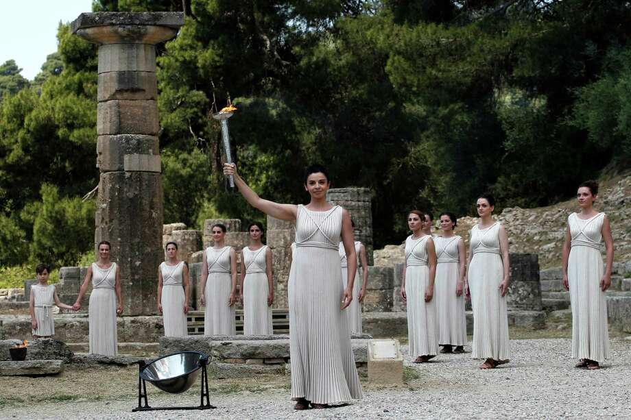 A high priestess, holds a torch with the Olympic flame during the lighting of the flame ceremony on Thursday, May 10, 2012, in Ancient Olympia, Greece.  The flame will be carried from the birthplace of the Ancient Olympics to London, where the 2012 Summer Games will take place from July 27-Aug. 12.  (AP Photo/Petros Giannakouri Photo: Petros Giannakouris, AP / AP