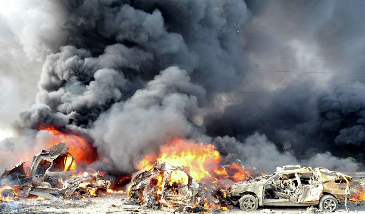 TOPSHOTS A handout picture from the Syrian Arab News Agency (SANA) shows smoke rising from burning cars at the site of twin blasts in Damascus on May 10, 2012. Two powerful blasts in quick succession rocked the Syrian capital at morning rush hour, killing and wounding dozens of people, state television said, blaming the attacks on