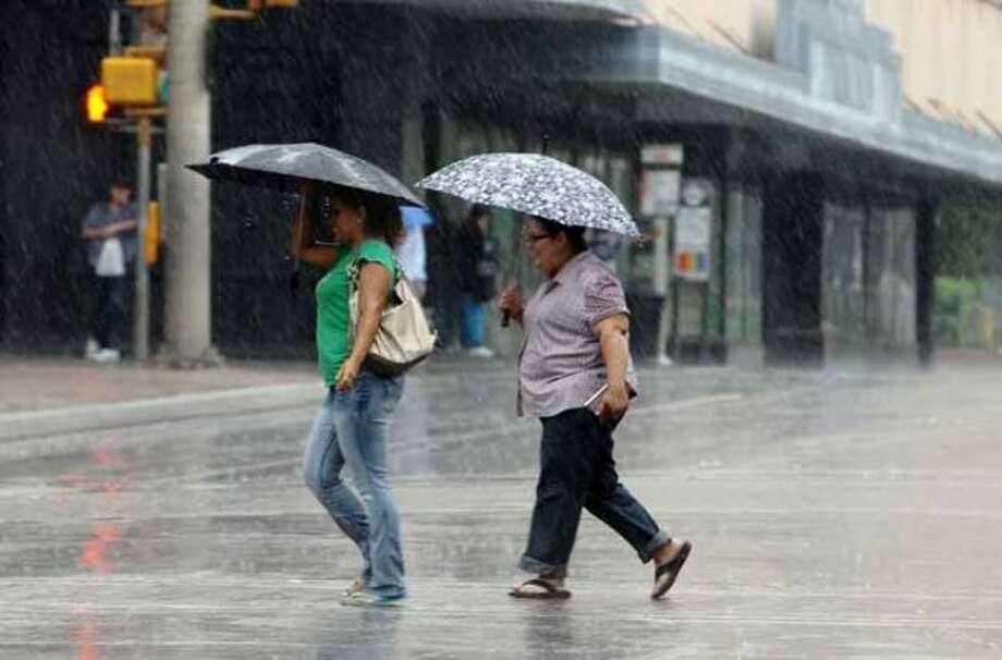 Seemingly unperturbed, two downtowners cross Commerce Street as rain starts to pour on Thursday, May 10, 2012. Kin Man Hui/Express-News (SAN ANTONIO EXPRESS-NEWS)